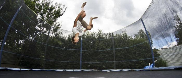 homme faisant salto sur un trampoline avec filets de protection